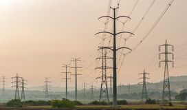 Electricity pylons over an arable land Royalty Free Stock Photos