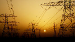Electricity Pylons over sunset Royalty Free Stock Images