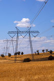 Electricity pylons. And overhead cables receding through countryside fields under blue cloudy sky Stock Photo