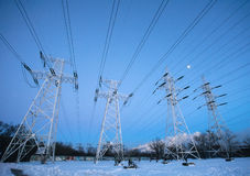 Electricity pylons and power high voltage tower in winter Royalty Free Stock Photography