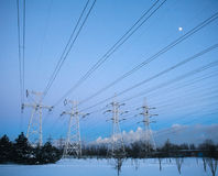 Electricity pylons and power high voltage tower in winter Stock Photos