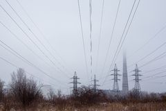 Electricity pylons, power lines and smoke stack in fog Stock Photography
