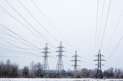 Electricity pylons and power lines in the winter day Royalty Free Stock Photos