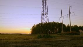 Electricity pylons and power transmission line panning. Sunset outumn evening. Outdoors handheld. Electricity pylons and power transmission line panning. Sunset stock video footage
