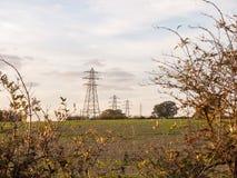 Electricity pylons row of far distance field farm agriculture Stock Photos