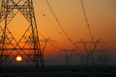 Electricity pylons with setting sun Royalty Free Stock Photos