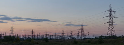 Electricity pylons silhouetted against the sunset Royalty Free Stock Images