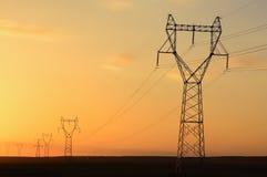 Electricity pylons at sunset Stock Photos