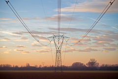 Electricity pylons at sunset. Electricity pylons silhouetted against the sunset Stock Photos