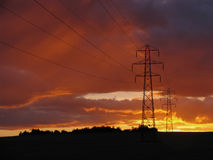Electricity pylons at sunset. Pylon silhouettes against a strong, warm sunset stock photos