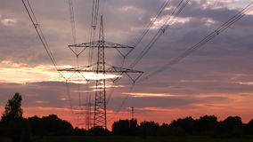 Electricity pylons in sunset time laps stock footage