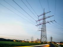 Electricity pylons at sunset transporting clean energy Royalty Free Stock Photography