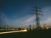 Electricity pylons at sunset transporting clean energy Stock Images
