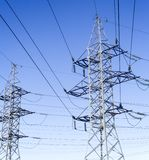 Electricity pylons. System of the electricity pylons against the blue sky stock images