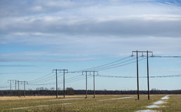 Electricity Pylons in Thawing Field Royalty Free Stock Image
