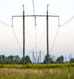 Electricity Pylons Trailing Away in Field. Power-transmission po. Les in the  nature environment Royalty Free Stock Image