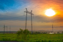 ELECTRICITY PYLONS. And wires in a green field against evening sky Royalty Free Stock Photo