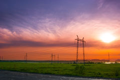 ELECTRICITY PYLONS_2. Electricity pylons and wires in a green field against evening sky Stock Image