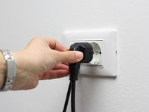 Electricity savings concept, woman unplugged plug. From the socket stock photos
