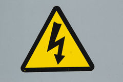 Electricity sign. A triangular sign with a black border and yellow background with a zig-zag arrow all on a grey background Stock Photos