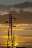 Electricity. Silhouette of high voltage power towers at sunset Stock Image