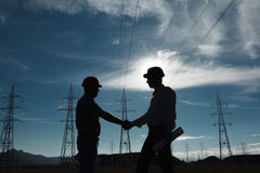 Electricity station handshake. Silhouette of engineers standing at electricity station shaking hands Stock Photography