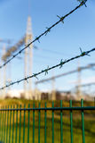 Electricity sub station behind barbed wire against blue sky stock photography