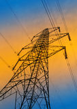 Electricity supply. Silhouette of electricity pylon against orange and blue sky stock image