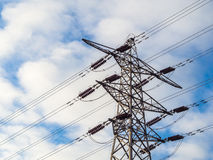 Electricity supply pylon against bright cloudy sky Stock Image