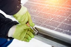 Electricity technician installing blue solar panels with screw. Photovoltaic modules as renewable energy source. Alternative energy production innovation Stock Photos