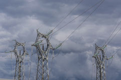 Electricity. Three electrical pylons on the background of a stormy sky Royalty Free Stock Photo