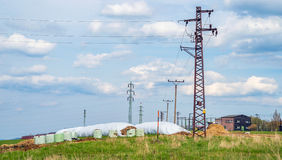 Electricity tower line power grid in countryside meadow hay heap Royalty Free Stock Photos
