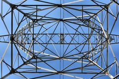Electricity tower. Symetric shape with a blue sky at background stock images