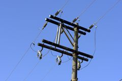 Electricity transmission pole. Under blue sky without cloud Royalty Free Stock Photography
