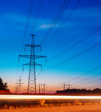 Electricity transmission power lines at sunset High voltage tower. Royalty Free Stock Photography
