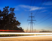 Electricity transmission power lines at sunset High voltage tower. Stock Photos