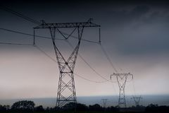 Electricity transmission power lines at sunset High voltage tower Stock Image