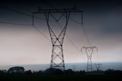 Electricity transmission power lines at sunset High voltage tower stock photography
