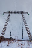 Electricity transmission power lines on winter background High voltage tower Stock Photos