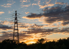 Electricity transmission pylon at city suburb against the sunset glow sky. Electricity transmission pylon at city suburb against the sunset glow sky Royalty Free Stock Images