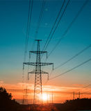 Electricity transmission pylon at city suburb against the sunset glow sky. Stock Images