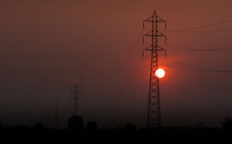 Electricity transmission pylon  in the field on sunset Royalty Free Stock Photo