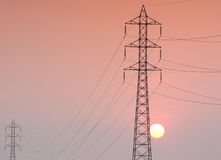 Electricity transmission pylon  in the field on sunset Stock Image