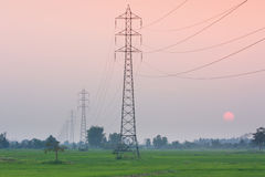 Electricity transmission pylon  in the field on sunset Royalty Free Stock Images
