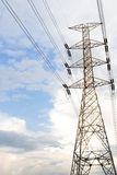 Electricity transmission pylon silhouetted against blue sky at d Royalty Free Stock Photo