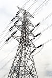 Electricity transmission pylon silhouetted against blue sky at d Stock Photo