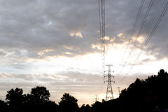 Electricity transmission pylon silhouetted against blue sky at d Royalty Free Stock Photography