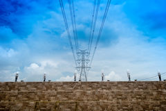 Electricity transmission pylon silhouetted against blue sky at d stock images