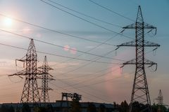 Electricity transmission pylon silhouetted against blue sky at dusk. stock photo