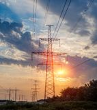 Electricity transmission pylon silhouetted against blue sky at dusk. stock image